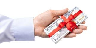 概念、金钱作为礼物,胜利或者奖金 人在衬衣的` s手采取或给堆100美金栓与与弓的红色丝带 免版税库存照片