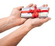 概念、金钱作为礼物,胜利或者奖金 人用两只手采取或给堆100美金栓与与弓的红色丝带 免版税图库摄影