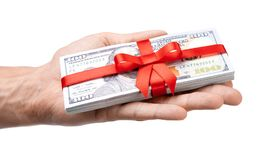 概念、金钱作为礼物,胜利或者奖金 人` s手采取或给堆100美金栓与与弓的红色丝带 查出 图库摄影
