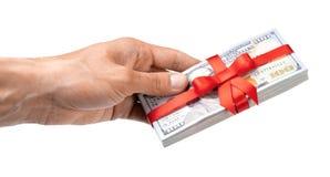 概念、金钱作为礼物,胜利或者奖金 人` s手采取或给堆100美金栓与与弓的红色丝带 查出 免版税库存照片