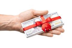 概念、金钱作为礼物,胜利或者奖金 人` s手采取或给堆100美金栓与与弓的红色丝带 免版税库存图片