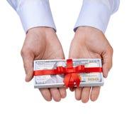 概念、金钱作为礼物,胜利或者奖金 人` s用在衬衣的两只手采取或给堆100美元和与弓的红色丝带 免版税图库摄影