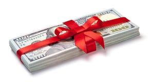 概念、金钱作为礼物,胜利或者奖金 堆100美金栓与与弓的红色丝带 查出在白色 免版税库存照片