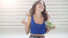 概念健康生活方式 微笑的运动的年轻女人用蔬菜沙拉在家 股票视频