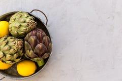 概念健康生活方式 朝鲜蓟和柠檬在圆的金属 免版税库存照片