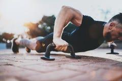 概念健康生活方式 户外培训 做俯卧撑的英俊的体育运动员人在公园在晴朗的早晨 免版税库存图片