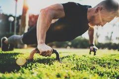 概念健康生活方式 户外培训 做俯卧撑的英俊的体育运动员人在公园在晴朗的早晨 库存照片