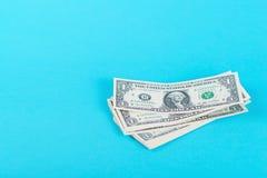 概念储款,财务,经济 一美元在蓝色backround隔绝的钞票 库存图片