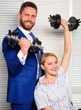 概念关键成功 男人和妇女提高重的哑铃 强的强有力的经营战略 上司商人经理 库存图片