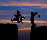 概念动画片剪影,人举行轴和人跳跃 免版税图库摄影