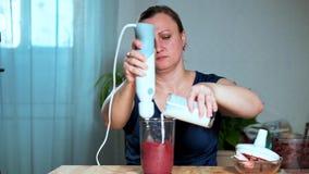 概念吃健康 妇女混合的果子和莓果纯汁浓汤的特写镜头用在搅拌器的酸奶 股票录像