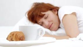 概念女性睡觉在床和白色咖啡上 奶油被装载的饼干 股票录像