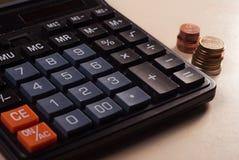 概念庄园房子货币实际反映 有硬币谎言的计算器在桌面上, 免版税库存图片