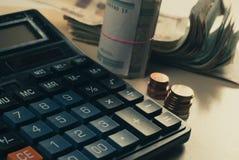 概念庄园房子货币实际反映 有硬币谎言的计算器在桌面上, 图库摄影