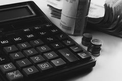 概念庄园房子货币实际反映 有硬币谎言的计算器在桌面上, 库存照片