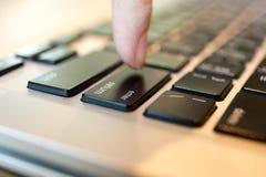 概念性人手指在膝上型计算机键盘上把输入按钮放 免版税库存图片