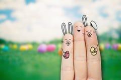 概念性复活节手指艺术 有的人两bunnys拿着两个被绘的鸡蛋 图象纵向股票妇女年轻人 库存照片
