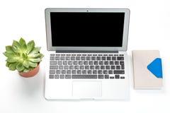 概念性工作区或企业概念 有植物的便携式计算机一个罐和笔记本的在白色背景 免版税库存图片