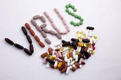 概念性手文字文本说明启发卫生保健健康概念写与药片使在白色的胶囊词病毒服麻醉剂 免版税图库摄影