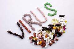 概念性手文字文本说明启发卫生保健健康概念写与药片使在白色的胶囊词病毒服麻醉剂 免版税库存图片