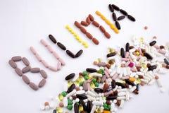 概念性手文字文本说明启发卫生保健健康概念写与药片使胶囊在丝毫的词善饥癖服麻醉剂 免版税库存照片