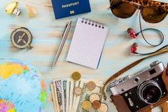 概念性旅行的辅助部件的游览飞行的图象在蓝色木背景的 免版税库存图片