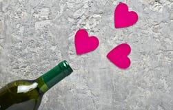 概念性照片瓶酒和桃红色装饰心脏 爱,浪漫概念,顶视图 免版税库存图片