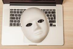 概念性照片,在一台膝上型计算机的面具作为黑客攻击的标志 免版税库存照片