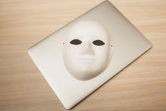 概念性照片,在一台膝上型计算机的面具作为黑客攻击的标志 库存照片