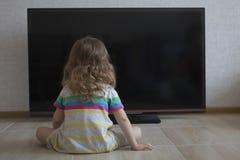 概念性画象 在家放置在地板和观看的电视的小女孩 免版税库存照片