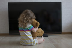 概念性画象 坐地板拥抱与在一个黑屏幕的背景的长毛绒玩具的小女孩 免版税图库摄影