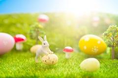 概念愉快的复活节 一点复活节兔子玩具和复活节彩蛋在绿草 在塑料绿色领域的童话日落与p 免版税库存图片
