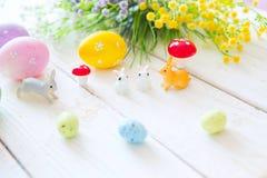 概念愉快的复活节 复活节与花的贺卡,复活节兔子兔宝宝在白色木板条戏弄并且怂恿 图库摄影