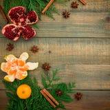 概念新年度 新鲜的可口石榴石、柑橘、桂香和茴香在木背景 平的位置 顶视图 圣诞节概念 免版税库存照片
