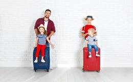 概念旅行和旅游业 带着手提箱的愉快的家庭临近w 免版税库存图片
