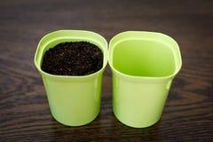 概念是空和充分的 两个花盆,一与地面,第二空 免版税库存图片