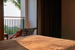 概念温暖的热带晚上在海滩的旅馆客房 晴朗的晚上光通过门户开放主义照亮床 免版税库存照片