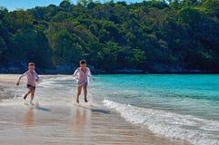 概念热带海滩的娱乐孩子 两个逗人喜爱的男孩在绿松石海海滩跑 复制空间 对广告 免版税库存图片