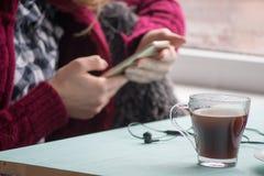 概念生活方式,咖啡馆的少妇喝和使用手机的在星期日早晨 免版税库存照片