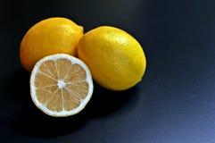 概念的三个柠檬,两整个和二分之一在黑背景 免版税图库摄影