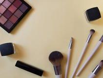 概念的化妆在桃红色背景的管和奶油色容器顶视图 唇膏,刷子,调色板 免版税库存图片