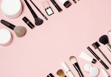 概念的化妆在桃红色背景的管和奶油色容器顶视图 库存图片