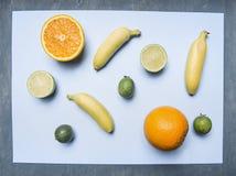 概念素食食物,新鲜的开胃果子,石灰,桔子,微型香蕉,排行在蓝色背景,维生素,顶视图 库存图片