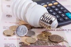 概念节能 电灯电灯泡、卢布金钱和计算器 免版税库存照片