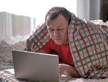 概念说谎在床上和键入在膝上型计算机的休息年轻人 库存图片