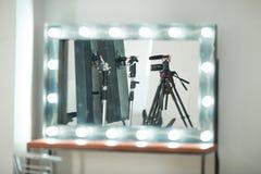 概念采访,在一个三脚架的数码相机有一个话筒的在白色背景的演播室在镜象反射 免版税库存照片