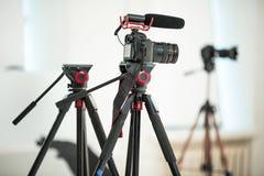 概念采访,在一个三脚架的数码相机有一个话筒的在白色背景的演播室 库存照片