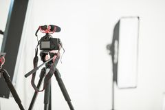 概念采访,在一个三脚架的数码相机有一个话筒的在白色背景的演播室 免版税库存图片