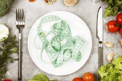 概念饮食食物 白色板材和测量的磁带 各种各样的菜和香料硬花甘蓝,胡椒,西红柿,大蒜 库存图片