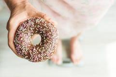 概念饮食 妇女在秤的` s脚特写镜头用多福饼 甜点、不健康的速食和肥胖病的概念 免版税库存图片